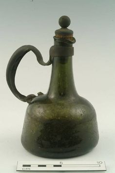 1700s Wine decanter bottle, natural green glass, slightly cloudy; flattened globular body; long neck with flared rim and folded spout; rounded basal edge, wide kick with unpolished pontil mark; original glass applied handle has broken away and been replaced with a metal handle, fixed to stump of old handle on the body, and a metal collar around the vessel neck. Location: Object stored at Mortimer Wheeler House (Ceramics and Glass store)