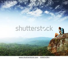 Young woman with backpack sitting on cliff and looking to a sky by Dudarev Mikhail, via Shutterstock