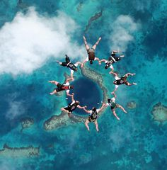 Skydivers form a circle over the Great Blue Hole.