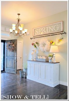 Dark wood floors contrast with the cream walls, white side cabinet, and spring sign making it a great statement for a foyer
