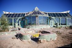 Phoenix House at the Earthship Biotecture community in Taos, New Mexico.  This home is 100% self-sustaining, completely off-the-grid, and only costs about $100 per year in utilities!  Made out of 100% recycled and reclaimed materials, the Phoenix gets its electricity from solar and wind. It gets its water from rain and snow, its heat from the sun and earth, and food from it's garden, fish pond, greenhouse inside the building.