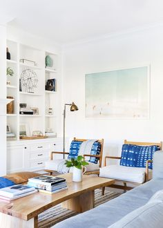 A bright and white living space with built-in bookshelves and woven armchairs with tie-dyed pillows