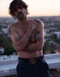 Tony Ward shows off his tattoos in a shirtless ensemble that features 3.1 Phillip Lim pinstripe linen trousers and a GG logo belt from Gucci.
