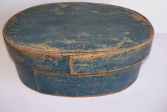 "BLUE OVAL PANTRY BOX  Large oval pantry or storage box in original dark blue paint.  This box appears to be Scandinavian as indicated by the straight stitched seams.  The box evidences wear appropriate to it's age and use.  The expected wear pattern and patina enchance the desirable blue painted surface.  This box dates to the early to mid 1800's.  13 1/2"" x 5 1/8""."