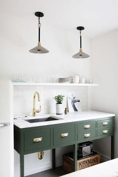 Kitchen with two industrial pendant lights, green cabinents, and gold fixtures