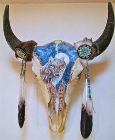 this is similar to the one I recently posted from the internet, however, this one is MY work. A yellowstone buffalo skull, hand painted, with beaded rosettes, imitation eagle feathers, and bone, shell, and turquoise beads. It is for sale.
