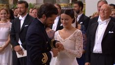 Prince Carl Philip uses a second hand in an effort to ease the ring into place with the entire world looking at the happy couple