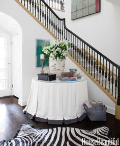 Brooke Davenport wanted the entry hall in her Los Angeles house to make a statement, so she used a graphic zebra rug from Melrose Carpet and a large table skirted with Scalamandré fabric; it also masks storage for big outdoor pillows. Sterling silver bowl, Oscar de la Renta Home. Walls in Benjamin Moore's Aura in Mayonnaise.