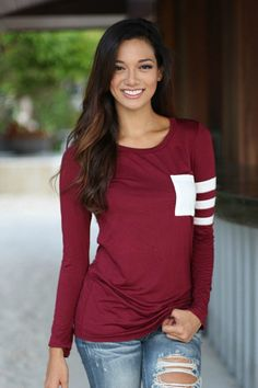 Tailgates and Touchdowns Pocket Tee. Get ready for weekend fun in our comfy Tailgates and Touchdowns Pocket tee.  Featuring a classic O neck with striped sleeve and pocket. This tee is super soft and perfect for those cool nights, it also looks great as a layering top. Available in Wine, Gray and Black. TheChicFind.com