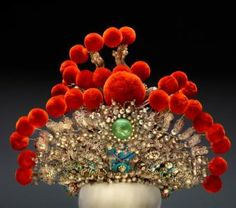 This Chinese theatrical headdress is created with pearls, blue kingfisher feathers, pompons, and other luxurious materials. Its rich colors and textures inspired Pinto to create an entirely new ensemble of  women's wear, exclusively displayed at The Museum's newest exhibition, Fashion and The Field Museum Collection: Maria Pinto.