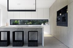 The kitchen is again committed to sleek simplicity with glorious marble countertops and bar stools that offer function but not at the expense of extreme, minimalist style.