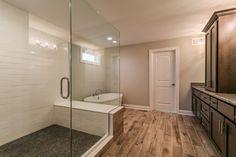Luxurious Master Bathroom with wood like custom tile and large oversized shower with white subway tile.