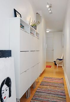 Struggling to decorate your long, narrow hallway? We have 19 long narrow hallway ideas that range in difficulty. From painting one wall to adding a long runner, we've got you covered. Turn your hallway into a library, or add shoe storage. Hallway Cupboards, Ikea Hallway, Hallway Shoe Storage, Hallway Cabinet, White Hallway, Long Hallway, Hallway Ideas, Shoe Storage Narrow, Ikea Shoe Storage