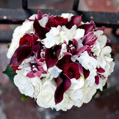 white hydrangea, dark purple calla lilies, purple mini orchids, & red roses