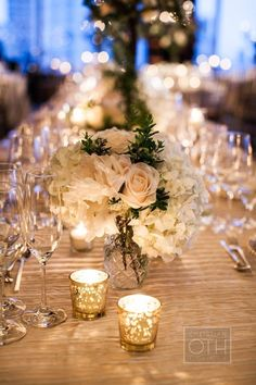I like the way the flowers are illuminated from the nearby candles.  I would want my flowers lower to the table and the candle holders to be not spotty (all champagne covered and/or clear or frosted)