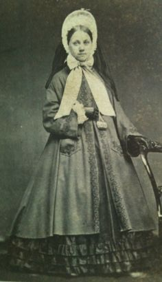 Lady with spoon bonnet and coat, carrying tiny purse. American civil war era fashion