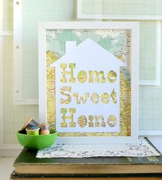 """Make any space feel more homey with the addition of this papercut artwork. The words, """"Home sweet home,"""" are carefully cut from textured white cardstock inside of a house shape and assembled over a vintage map page. Bodies of water and/or landmasses from the map peek through the cutout, for a layered, one-of-a-kind art piece."""