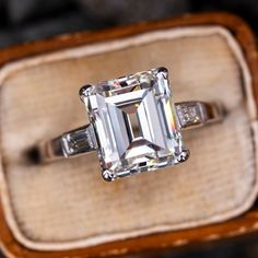This magnificent emerald cut diamond engagement ring features French hallmarks and is set with an incredible carat center diamond. The diamond grades a breathtaking H color and clarity. It is completely eye clean with a bright beautiful shimmerin Emerald Cut Diamond Engagement Ring, Emerald Cut Diamonds, Antique Engagement Rings, Diamond Wedding Rings, Diamond Cuts, Marquise Diamond, Wedding Bands, Antique Diamond Rings, Vintage Diamond