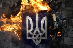 Ukranian coat of arms burns outside the prosecutor's office in Donetsk May 1, 2014. Pro-Russian protesters stormed the prosecutor's office in the separatist-held city of Donetsk on Thursday, lobbing stones and smashing windows after accusing the office of working for the Western-backed government in Kiev.