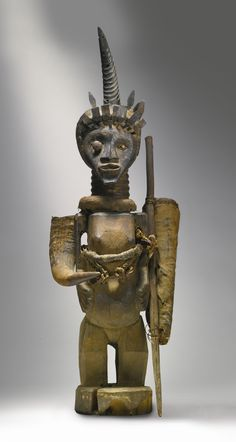 Songye Power Figure, Democratic Republic of the Congo with an African Buffalo (Syncerus caffer) horn attached at the right arm, a strap with African Royal Python (Python regius) skin across the chest, a quiver on the left shoulder covered with Reedbuck Antelope (Redunca redunca) hide, and a Reedbuck Antelope (Redunca redunca) horn surmounting the head.  Height: 36 1/2 in (92.5 cm)  READ note
