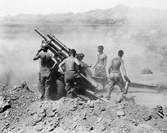 Gun crew of the 25th Infantry Division fire a 105 mm howitzer on North Korean positions near Uirson, in Korea on August 27, 1950.