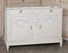 Antique Louis XVI Painted Marble Top Buffet.  For a subtle, understated elegance, the Louis XVI style can be unequalled, and this superb buffet is a great example. Crafted from solid French walnut, it features carved embellishments only at the top of the door panels as well as on the rounded cornerposts. The remainder of the elegance stems from the beautifully patinaed painted finish, the tailored architecture, the beveled Cararra marble top, and the cast bronze pulls & keyguards.