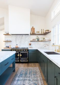 Bright kitchen features high ceilings marble counter tops and backsplash and open wooden shelves in this home located in Ojai California. [1280 1816]