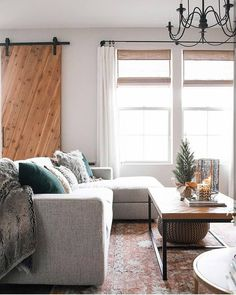 Winter / holiday living room: forest green pillows, soft faux fur throws & pillows, lanterns / candlelight.