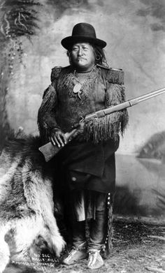 Studio portrait of Chief Nautzille (Nallti Zilli), Mescalero Apache man wearing a buckskin leggings and shirt with epaulets and fringe, moccasins, and a domed felt hat; he holds a rifle. Description from pinterest.com. I searched for this on bing.com/images