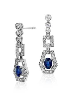 These deco-inspired drop earrings feature beautiful oval sapphire gemstones set within a pavé diamond drop design.