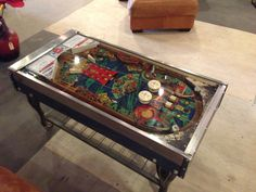 vintage industrial pinball coffee table by rogue decor co.  custom welded lower shelf with vintage stove legs with casters.  rewired and runs off rechargeable battery, so no messy cord to trip over.  pull the ball plunger to turn lights on/off. www.facebook.com/rogue.decor