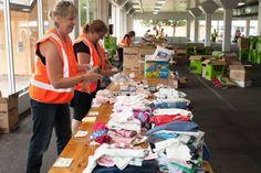 Teresa Robertson and Liza Huston fold and sort donations at the Wayville Show Grounds for Sampson Flat bushfire victims. (ABC: Brett Williamson)
