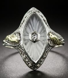 Art Deco Carved Quartz and Diamond Ring, A pair of small golden birdies keep watch over a shimmering, navette shape carved frosted quartz crystal, pierced in the center with a single sparkling diamond, in this very lovely and unusual depression-era delight. Die struck in 10K white fold filigree- circa 1930.
