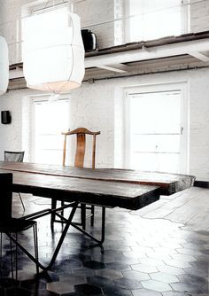 Everything about this is great: awesome tile to wood transition, brilliant table, cool lamps, great walls and windows....