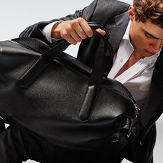 The Large Weekender in black grained leather with suede leather…