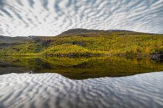Autumn colours glassy lakes and interesting clouds in Norway. by drifterphotos