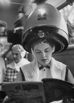 woman reading a magazine at a beauty parlor.