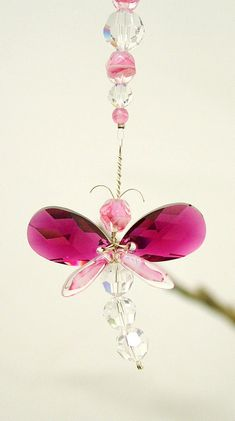 This striking pink dragonfly suncatcher / car charm has been hand crafted from Swarovski Crystal & glass beads. This charm gives a great sparkle in sunlight. Place it hanging from a wish tree in a wedding, or car's rear view mirror, near a window or hanging in the middle of the room. The possibilities are endless ... ! It makes for a great gift. Each dragonfly has its own character, they are one of a kind, as they are individually created by hand, making each dragonfly unique.  Keep out of…