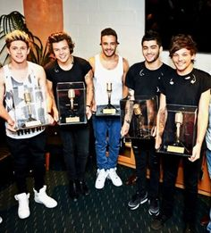 The boys holding their awards for breaking the record of most tickets sold at Allphones Arena FML