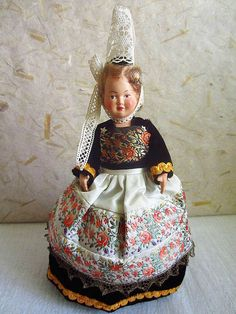 "This pretty celluloïd doll is wearing the typical tall headdress called a Bigoudène, from Brittany's Bigouden Country, in the department of Finistère, around the town of Pont-l'Abbé. She wears a velvet all black dress with orange trimmings , a wide white apron decorated with a large ribbon of stitched flowers. She has a piece of the same ribbon but in black pinned across her chest. Typical Pont-L'abbé costumes also include bright orange and yellow trimmings called ""triskell"", but this doll…"