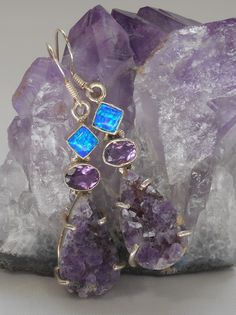 Natural Amethyst specimen gemstones accented with faceted Amethyst ovals and vibrant square polished Fire Opals, set in 925-hallmarked sterling silver. Matching pendants available separately. Total ea