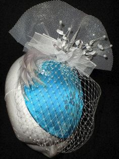 AVAILABLE NOW - Perfect for the Mother of the Bride - a medium round sinamay base covered in oriental turquoise and white satin.  Comes completed with white netting and tulle. Decorated with a spray of Baby's Breath and pearls and a white feather.  Finished at the back with a large white bow.  $60.00 plus Postage :♥:  Email your postal details to info@madebyrose.net Payment is through PayPal only
