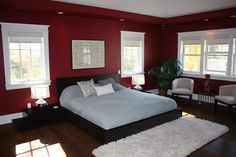 I want a red bedroom. Simple like this, but with tall black-framed windows instead of crisp white, and black shading too. And please remove the the white rug. While you're at it, replace the white chairs with black ones. The only white stuff here should be the bed and the lampshades. The cabinet and boudoir would be black too.