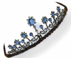 A sapphire and diamond tiara/necklace  Composed of a series of graduated oval-cut sapphire and diamond cluster motifs, with old brilliant-cut diamond scrolling crescent accents and diamond single stone detail, circa 1900, detachable to be worn as a necklace, in fitted case