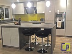 Contemporary design - German kitchen with a pop of colour yellow glass splashback.