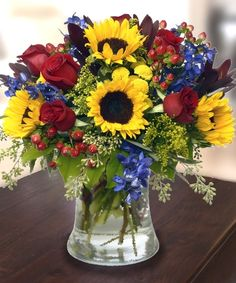 Tuscany Bouquet, Bright yellow #Sunflowers, Pale Blue #DelphiniumBlossoms, #RedRoses. http://www.carithers.com/flowers/Sunflowers-Delphinium-Roses-Tuscany-Arrangement-TF233P/