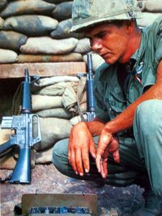 A photograph of a soldier next to the incredibly rare Colt Model 607. Only 50 copies of the assault rifle would ever be produced, and only 25 ever made it into Vietnam-and by all indications, they wound up directly in the hands of Navy SEALs. No caption has yet been found for the photo, so it remains a mystery as to why a grunt is resting near this exceedingly rare firearm.