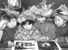 Children of Oroqen ethnicity with traditional roe deer skin caps reading a picture book. (Heilongjiang Province)