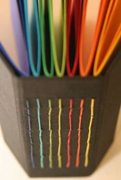 Long stitch binding with rainbow signatures and matching stitching #bookbinding