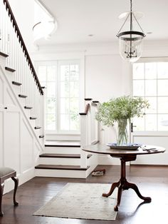 White walls, trim and ceilings let this entryway speak for the mood of the home: clean and understated.  A white backdrop is the perfect way to let the furniture, lighting and accessories take center stage.